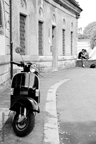 Black and white photo of an iconic scooter with a young couple in the background. #87046889