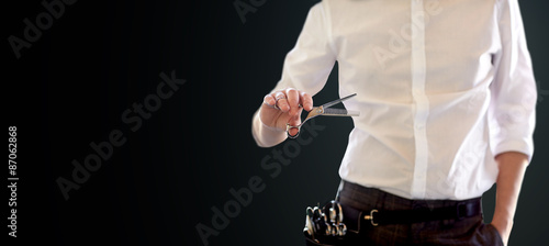 close up of male stylist with scissors over black