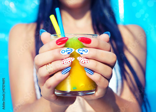 Young woman with marine sailor manicure holding glass of orange juice, summer na Poster