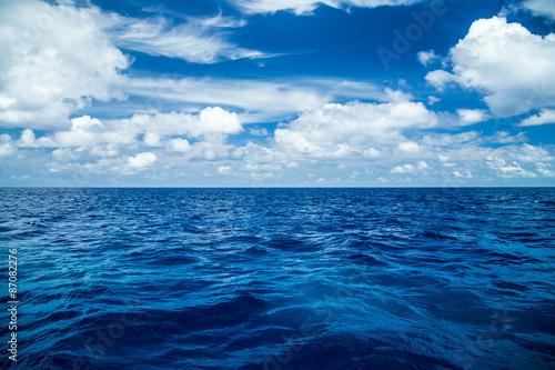 Fotografija  blue ocean background with blue cloudy sky