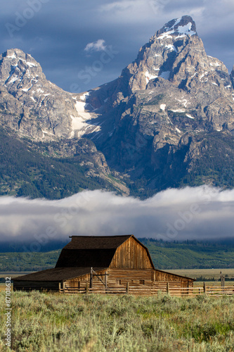 Photographie Iconic barn in Mormon Row with fog over the snake river and mountains in Grand T