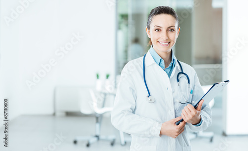 Smiling female doctor holding medical records Fototapet