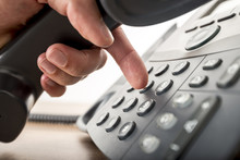 Closeup Of Dialing A Telephone Number On A Black Landline Teleph