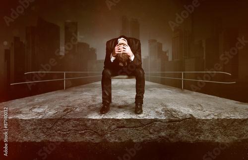 Sad man sitting on a broken street