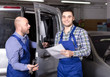 Mechanic and insurance agent at workshop