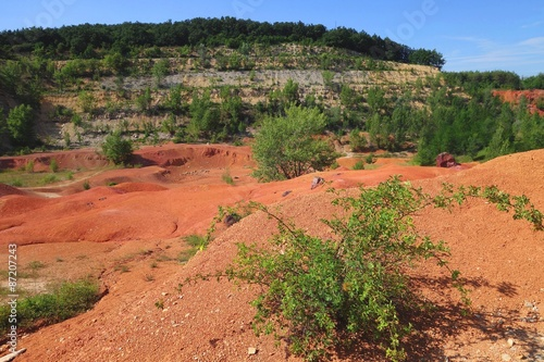 Foto op Canvas Baksteen Old out of use open-pit bauxite mine in Gant Hungary with green vegetation