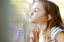 Funny Girl Kissing Her Reflection On A Window