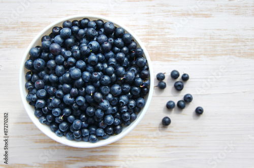 Fotografija Fresh bilberry in a white ceramic bowl on a wooden surface