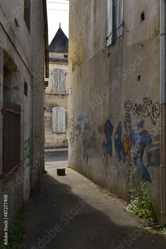 Poster Smal steegje Graffitis sur le mur d'une maison dans un passage étroit