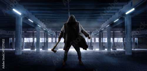 Canvas-taulu Man with axe waiting in public parking garage