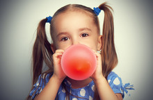 Little Girl In Blue Dress Inflates Red Balloon