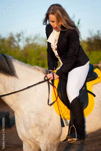 Fotografie, Obraz Horsewoman at hippodrome and blue sky