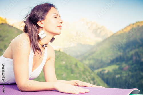 Beautiful woman relaxing and meditating outdoor at swiss mountain. She lies at peak of mountain and feel harmony of your body and nature. Healthy lifestyles concept of body and soul
