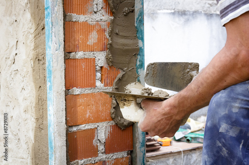 Staande foto India Obreros de la construcción trabajando en obra. Obras en el hogar. Reforma de fachada. Trabajador luciendo la fachada de una casa.