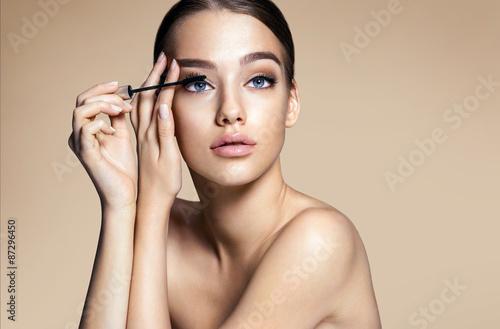 Valokuva  Woman applying black mascara on eyelashes with makeup brush / photos of appealin
