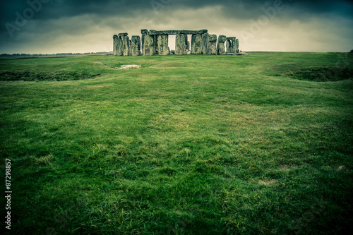 Grass field leading to Stonehenge on a cloudy gray day