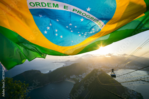 Deurstickers Rio de Janeiro Brazilian flag shines above the golden sunset city skyline at Sugarloaf Pao de Acucar Mountain in Rio de Janeiro Brazil