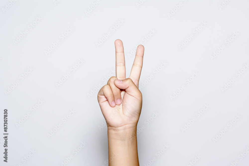 Fototapeta Boy raising two fingers up on hand it is shows peace strength fight or victory symbol and letter V in sign language on white background.