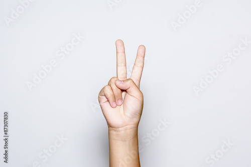 Boy raising two fingers up on hand it is shows peace strength fight or victory symbol and letter V in sign language on white background Fototapet