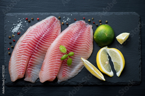 Photo  Stone slate plate with raw tilapia filets, view from above