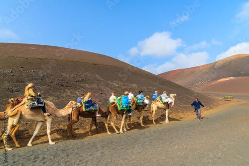 Spoed Fotobehang Kameel Caravan of camels with tourists in Timanfaya National Park, Lanzarote, Canary Islands, Spain