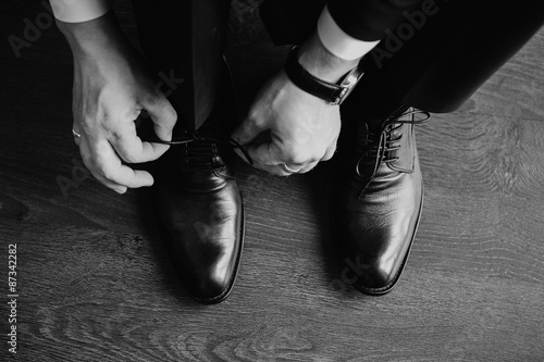 Fotografia  Business man dressing up with classic, elegant shoes. Groom