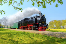 Historical German Steam Train Passes Through The Fields In Sprin