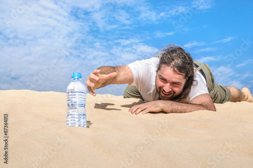 Photo Thirsty man in the desert reaches for a bottle of water
