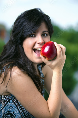 Valokuva  Half-length portrait of young woman eating red apple / Half length portrait of a