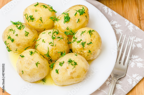 Traditional Ukrainian food boiled new potatoes with butter and dill on wooden ta Fototapeta