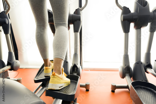 Fotografie, Obraz  Closeup of a woman using a stepper and training in a gym