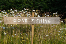 Gone Fishing Sign Among Flowers