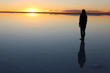 ウユニ塩湖の夕焼けと人