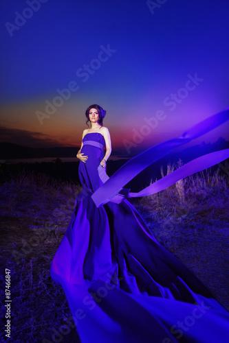 Fototapeta Portrait of beautiful woman in blue clothes standing at top hill obraz na płótnie