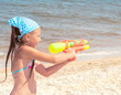 Girl with a water pistol on the beach