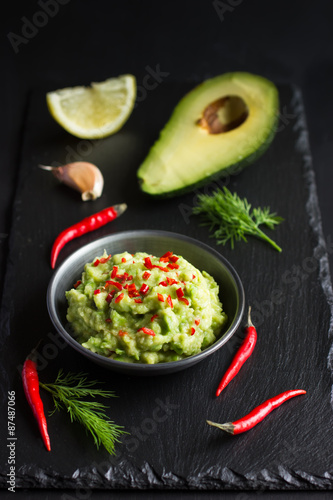 Photo  Guacamole dip and ingredients on black background