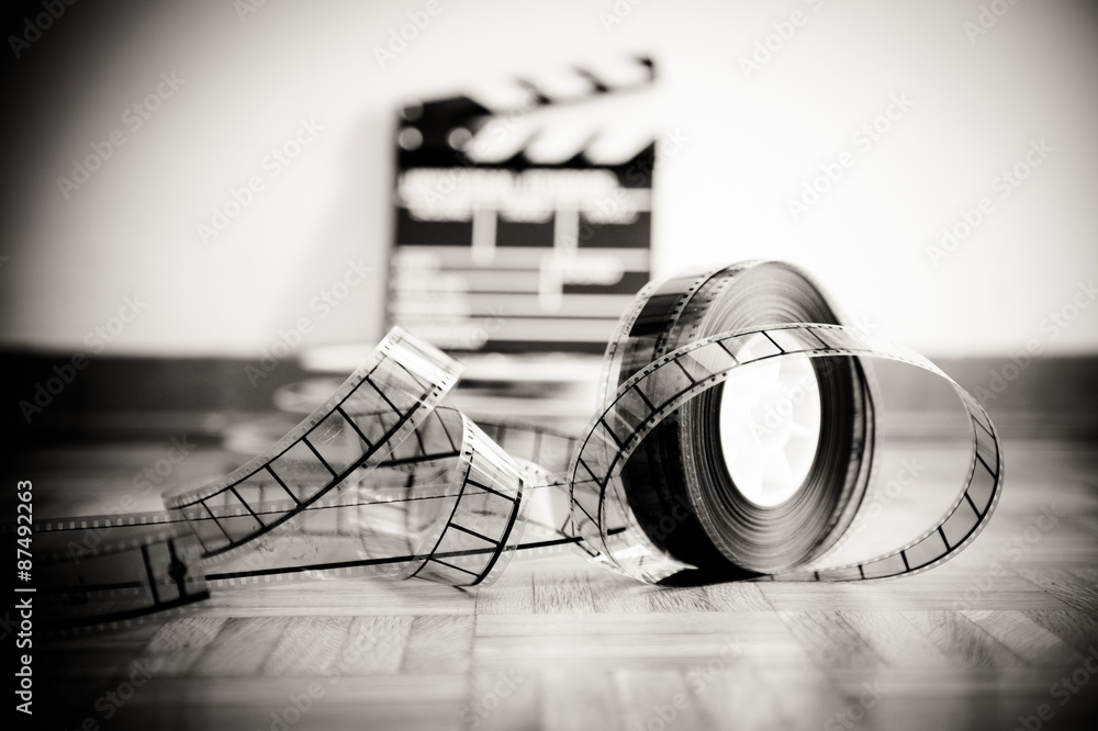 Fototapeta Cinema film reel and out of focus movie clapper board