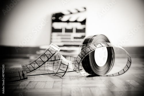 Fotografering  Cinema film reel and out of focus movie clapper board