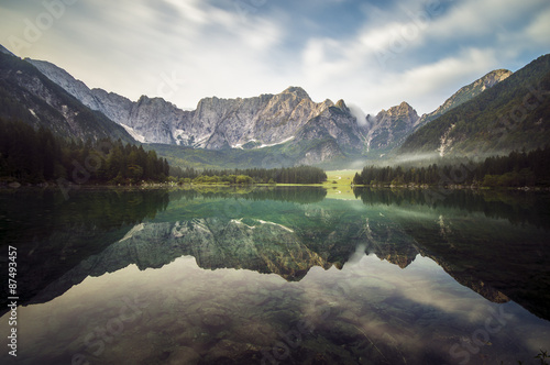 Door stickers Reflection alpine mountain peaks reflecting in a mountain lake