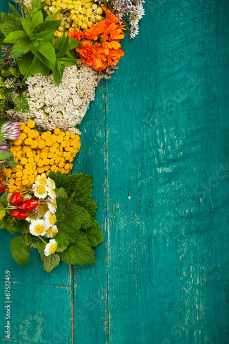 Photo  Summer fresh medicinal herbs on the wooden background.