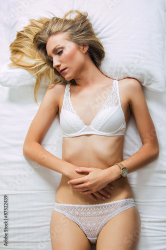 Sexy Girl In White Lace Underwear Lying On The Bed Looking Sad