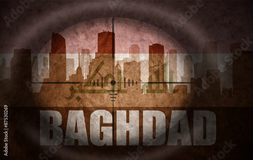 Fotografija  sniper scope aimed at the abstract silhouette of the city with text Baghdad at the vintage iraqi flag