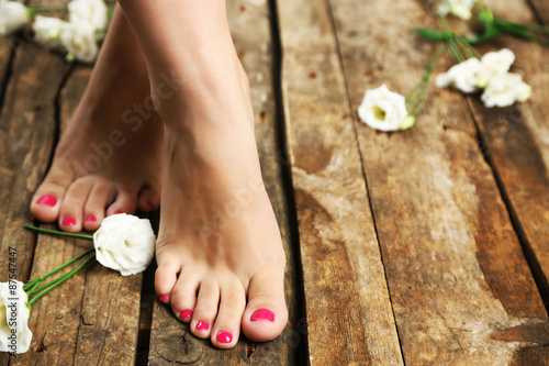 Foto op Aluminium Pedicure Beautiful female legs on rustic wooden floor background