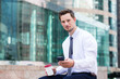 Young Businessman sitting with coffee and smartphone at Hong Kon