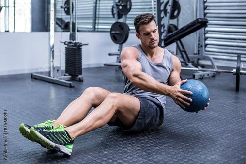 Fotografie, Obraz  Muscular man doing russian twist exercises