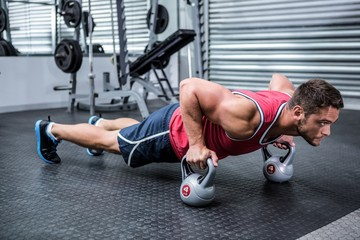 FototapetaMuscular man doing push-ups with kettlebells
