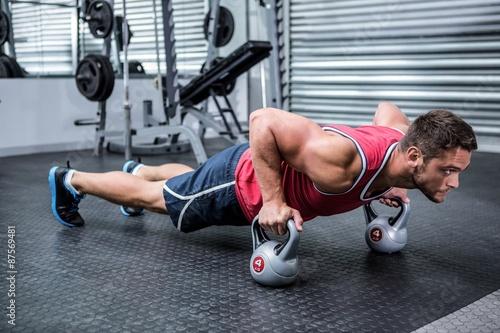 Muscular man doing push-ups with kettlebells - 87569481