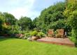 Leinwandbild Motiv sommerlicher Garten mit Gartenmöbeln