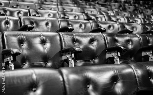 Raked seating. Full frame detail from rows of raked leather seating of the type found in conference or concert halls. - 87584415