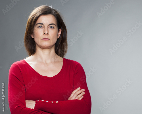 serious young woman with brown hair and red sweater staring with arms crossed fo Fototapet